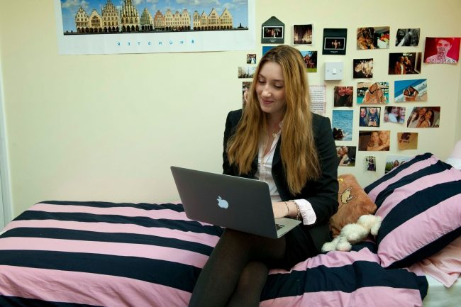 High school student working from laptop in bedroom in boarding house of a UK private boarding school in England