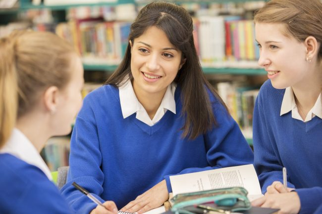 students work together in the library of a British high school