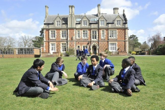 British children and international exchange students playing together at school in England