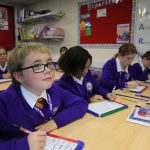 British children and international exchange students studying together at school in England