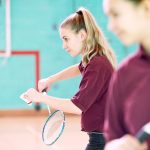 Girls playing badminton during sports class in a UK high school