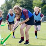 Girls playing hockey during sports class in a UK high school