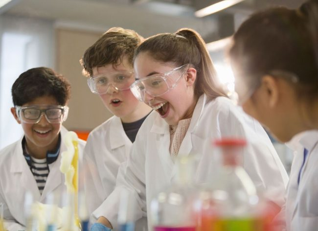 UK high school students and international exchange students enjoying science class in a British state boarding school